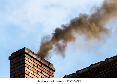 smoke billowing / coming out of a house chimney against a blue sky background