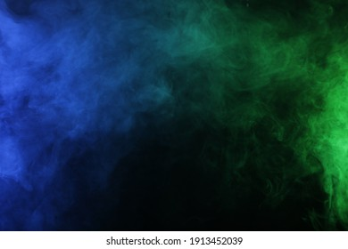 Smoke in blue green light on black background in darkness