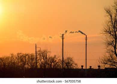 Smoke from the boiler pipes at sunset. Winter landscape.