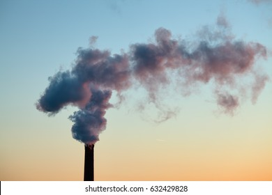Smoke from the brick chimney of the plant in the early morning. The smoke from the pipe cogeneration plant. Ambient air pollution industrial emissions