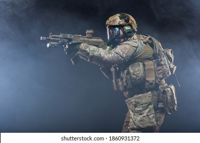 Smoke from chemical weapons and tear gas impair the visibility of a soldier in full military gear, helmet, bulletproof vest and gas mask, holding a machine gun and aiming at the enemy, side view