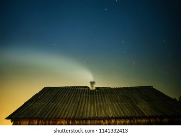 Smoke from the chimney at moon night. Smoking chimney in winter forest at night. Old rural roof under starry sky in mountains