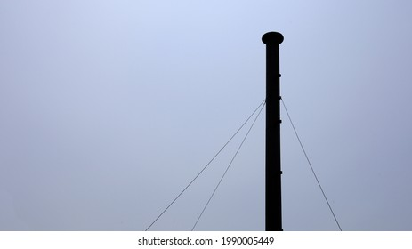 Smoke chimney silhouette. Metal chimney on blue sky background during rainy season with copy space. select focus