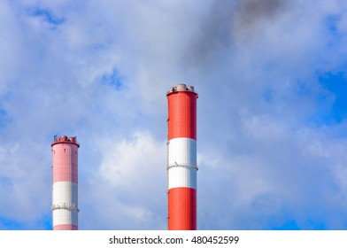 The smoke from the chimneys against the blue sky with clouds