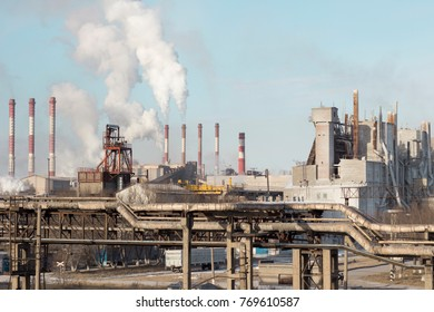 The smoke from the chimneys against the blue sky. Metallurgical combine