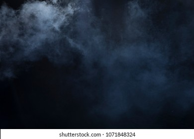 Smoke clouds create fog over top left and bottom right of black background