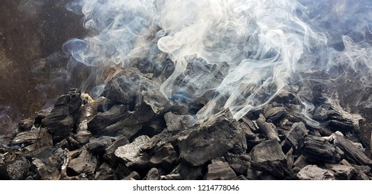 Smoke of the coal on the embers. Preparation of fire for barbecue embers. Outdoor recreation. No flames seen in the image.