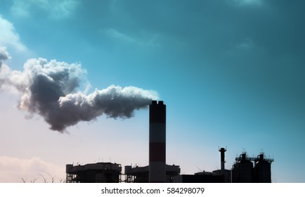 Smoke comes out of factory chimneys / environment and industry and air pollution, dust, smog, fine dust
