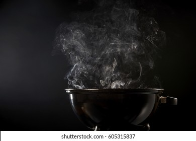 Smoke coming from a hot barbecue fire in a low angle view of a small circular portable black grill over a dark background with cop space