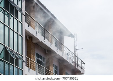 The smoke coming out of the front of the high building due to a fire.