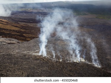 Smoke coming out of the ground of the lava field at the foot of the Puu Oo vent, Big Island, Hawaii. Aerial photograph out of a helicopter.