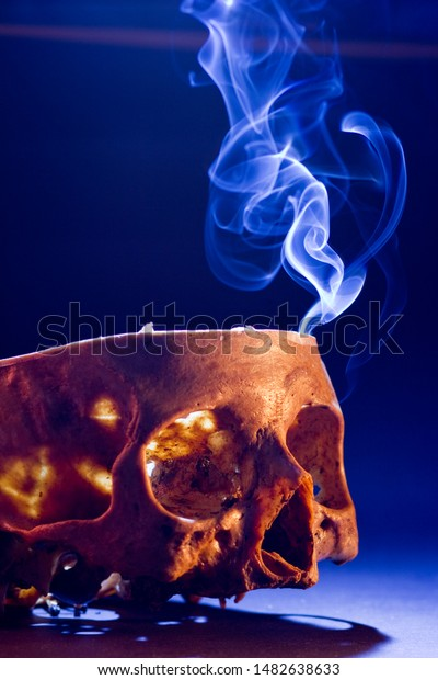 Smoke coming out of a skull cut in half over a table.