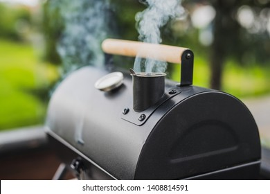 Smoke coming out of a smokestack of a small black smoker grill or barbecue on green background.
