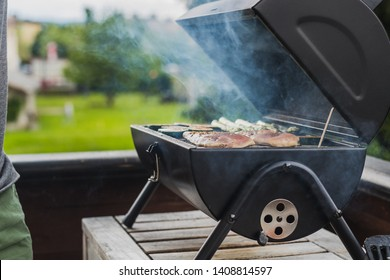 Smoke coming out of a smokestack of a small black smoker grill or barbecue, loaded with chicken meat and vegetables.