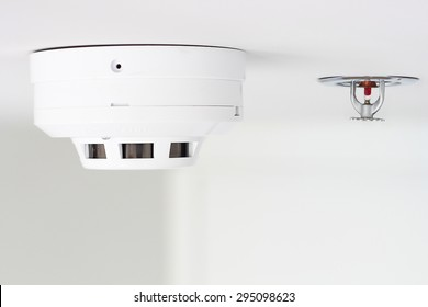 smoke detector and pendent fire sprinkler on a ceiling
