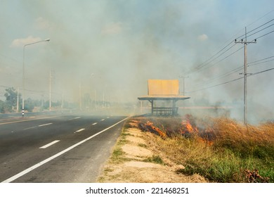 Smoke from fire blowing across gravel road Thailand