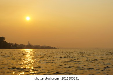 Smoke from forest fires enveloped lake coast of city in summer day