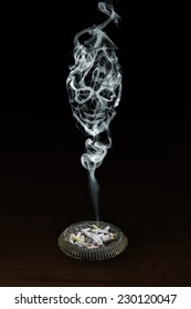 The smoke in form of a of the skull rising above ashtray with cigarette butts and a burning cigarette.