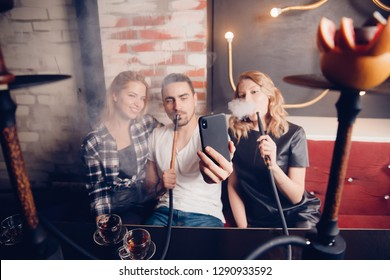 Smoke hookah shisha in bar and nightclub, team of friends take selfie photos on phone.
