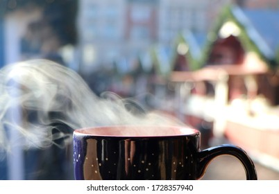 Smoke of a hot drink with Christmas market as blurry background, copy space