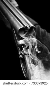 Smoke from a hunting double barrel vintage shotgun after firing.Comcept hunting.Closeup.Black and white