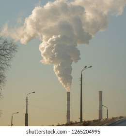Smoke from industrial chimneys against the blue sky. Pollution.