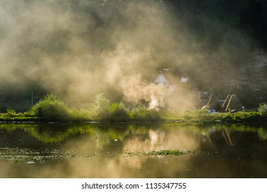 Smoke mirroring/Danube shore in Serbia with a house and haystacks where the Golden lit by sunset smoke is mirroring in the water surface.