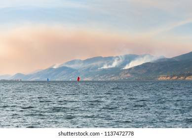Smoke from multiple forest fires in the mountains above Naramata viewed from across Okanagan Lake