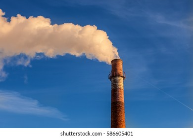 Smoke from the old pipe CHP a blue sky background at sunset. Ambient air pollution (environmental) industrial emissions