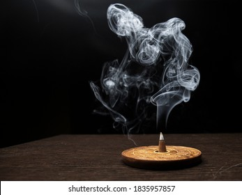 Smoke on dark background from burning cone incense standing on wooden incense holder