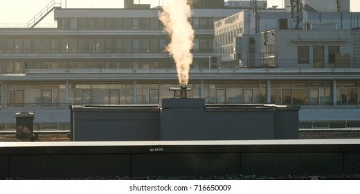 Smoke over a chimney in a industrial area in the backlight