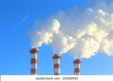 Smoke from pipes of a gas boiler room and the flying by plane in the sky