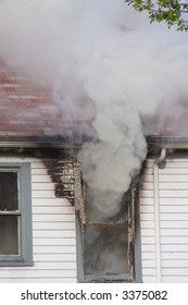 Smoke pouring out of the second story window in a house that is on fire
