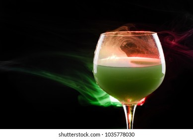 Smoke pouring out of wine glass with green liquid or cocktail and red light isolated on black background with copy space. Smoke above alcohol. Saint Patrick's symbol.