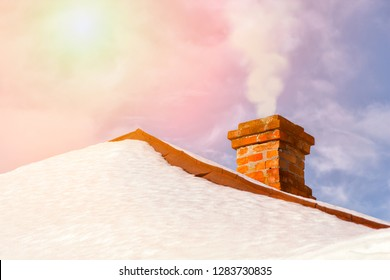 Smoke raising from a chimney in snny winter