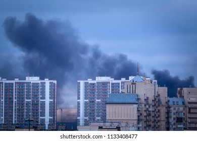 Smoke rises above the houses. Fire. Fire in houses. Black smoke from a fire.