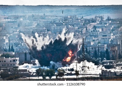Smoke rises from the Syrian city of Kobani, following airstrikes by the US led coalition, seen from a hilltop outside Suruc, on the Turkey-Syria border 12 OCTOBER 2014