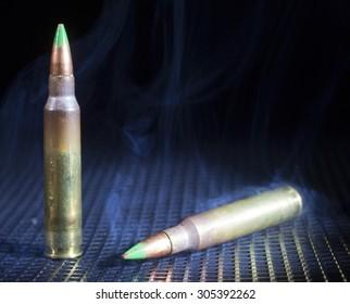 Smoke rising up around a pair of armor piercing rifle cartridges