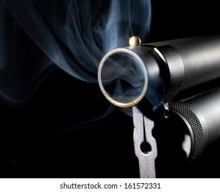 Smoke rising from the barrel of a black shotgun