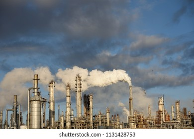 Smoke rising from an industrial oil and gas refinery with a complex arrangement of smokestacks and metal pipes near Corpus Christi, Texas / USA.