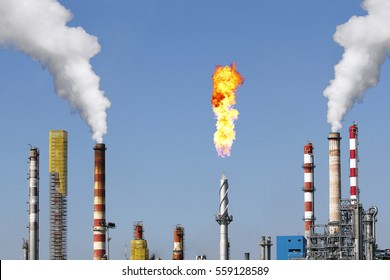 Smoke stacks and combustion gas torch in a large oil refinery