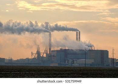 Smoke stacks emitting gases into the atmosphere. Smoke from factory over city in sunrise