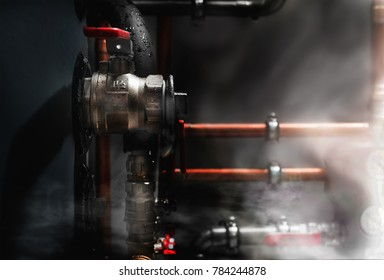 Smoke and steam in a boiler room. Copper pipes and valves on a wet boiler