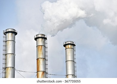 Smoke and steam coming out from an industrial petrochemical plant chimney with a blue sky on the background