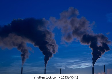 Smoke, steam, or gas billowing from industrial smokestack chimneys into the cold blue morning air.