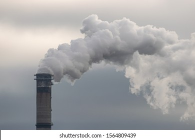 Smoke and steam produced off from the chimney against dark stormy sky