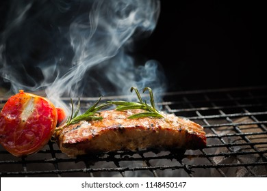 Smoke and steam rise from a pork steak on the grill