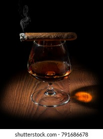 smoked aromatic cigar and a glass of cognac on a black background