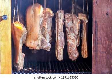 Smoked bacon hanging in wooden smoker