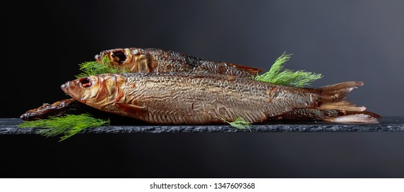 Smoked Baltic herring with dill on a black background. Copy space for your text.